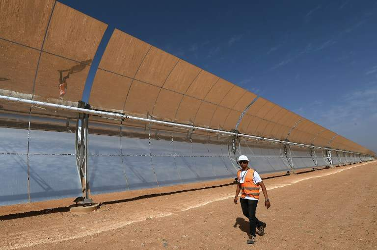 A Moroccan worker walks in front of a solar array that is part of the Noor 1 solar power project in Ouarzazate on October 19, 2014. Morocco's first solar energy plant will begin operating in 2015, an official said, as part of a multi-billion-euro project the oil-scarce kingdom hopes will satisfy its growing energy needs. The Nour 1 plant cost 600 million euros (USD 765 million) and is expected to have a capacity to generate 160 MW. AFP PHOTO/ FADEL SENNA
